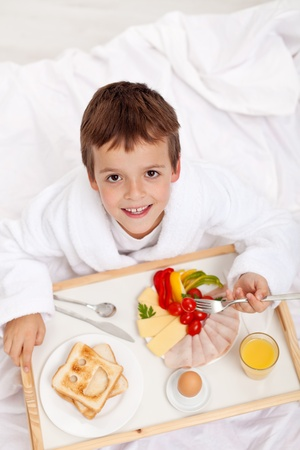 ni�os desayuno: Infantil por la ma�ana feliz de tener el desayuno en la cama Foto de archivo