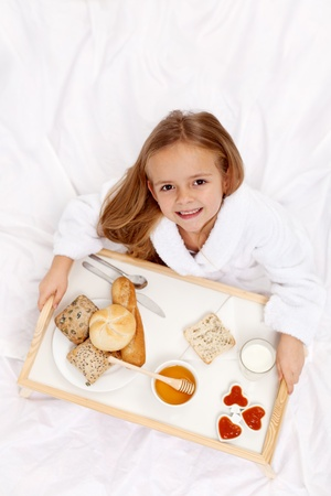 light breakfast: Happy little girl having a light breakfast in bed - top view Stock Photo