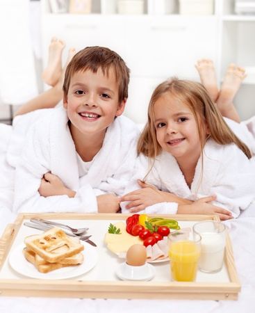 Happy healthy kids having a light breakfast in bed photo