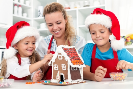 Our christmas gingerbread cookie house - family in the kitchen at holidays time Stock Photo