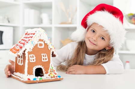 My christmas gingerbread cookie house - little girl in the kitchen at holidays photo