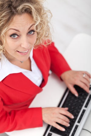 cheerfully: Smiling woman in the office looking up cheerfully Stock Photo