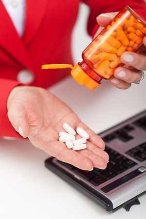 Taking pills in the office - woman fighting fatigue, headache or flu Stock Photo - 11411319