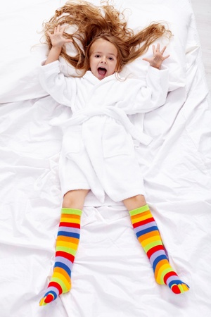 The thrill of a great morning - little girl waking up happy photo