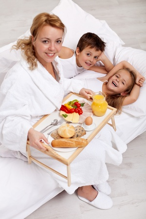 Happy morning and healthy food - mother bringing breakfast to bed for her kids photo
