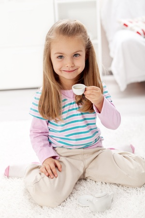 sitting on floor: Beautiful litlle girl having a cup of tea playing with miniature tea set in her room