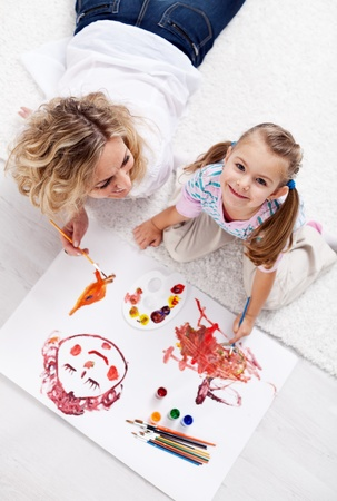 Painting with mom - little girl with brush and colors Stock Photo