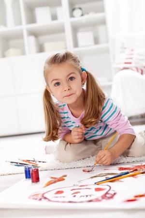masterpiece: Little artist girl painting a masterpiece kneeling on the floor Stock Photo