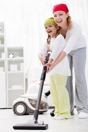 clean hand: Cleaning up the room together - woman and little girl with vacuum cleaner