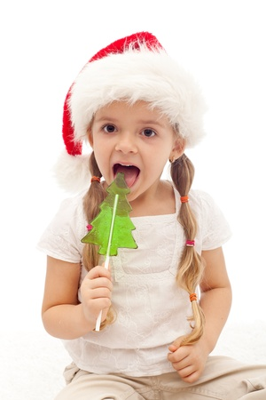 Happy Christmas girl licking a fir tree shaped candy - isolated