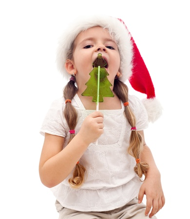 Little girl busy licking a christmas tree shaped candy - isolated Stock Photo - 12477445