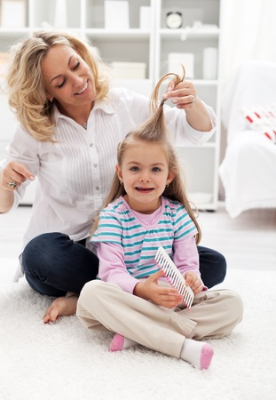 Girls beauty ritual - woman and child combing hair at home photo