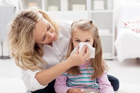 ragazza malata: Donna a casa soffiarsi il naso della sua bambina