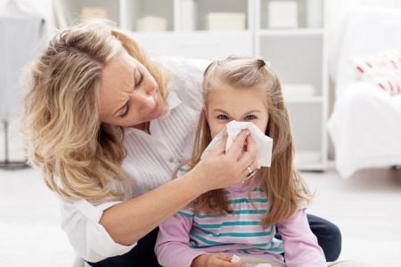 Woman at home blowing the nose of her little girl photo