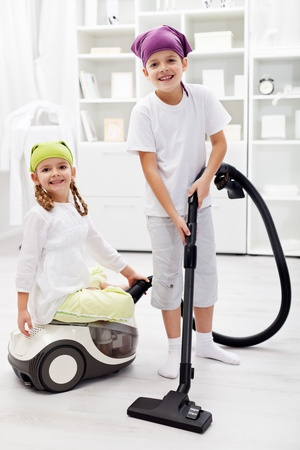 Tidy up day - children cleaning their room using the vacuum cleaner photo