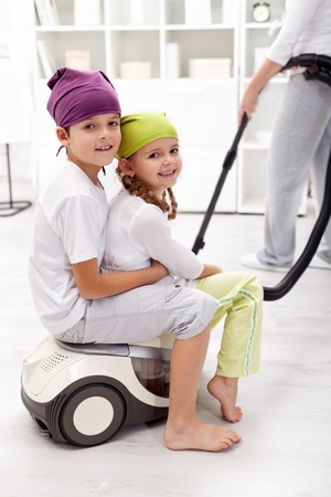 Kids having fun helping their mother cleaning the room photo
