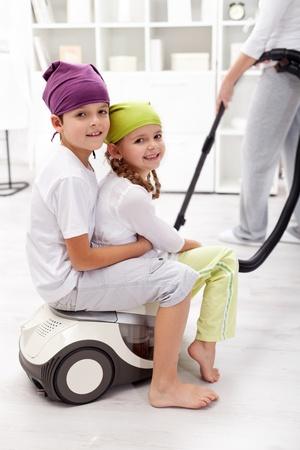 Los niños se divierten ayudando a su madre la limpieza de la habitación Foto de archivo - 12030707