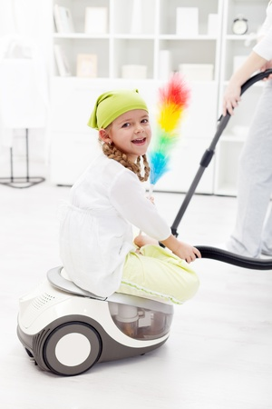 Little girl helping mother to clean the room - sitting on the vacuum cleaner Stock Photo - 12068079