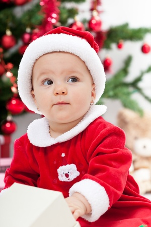 Beautiful baby girl in front of the christmas tree wearing santa clothes - closeup Stock Photo - 12078506