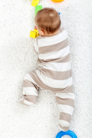 six months: Baby crawling on the floor - top view