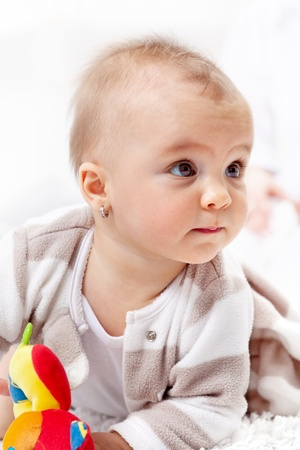 Beautiful baby girl crawling on the floor with a curious look - closeup Stock Photo - 12078508