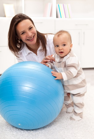 Baby girl stands by a large ball with a little help from her mother Stock Photo - 12068103