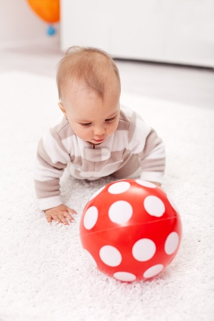 six months: Baby girl crawling on the floor chasing a red ball Stock Photo