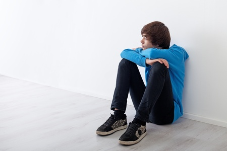 depression man: Serious teenager boy thinking and daydreaming while sitting at home