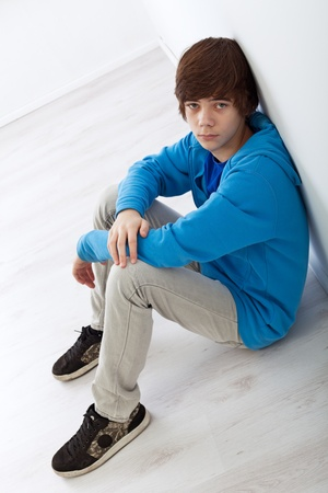 Sad teenager boy sitting on the floor leaning against the wall photo