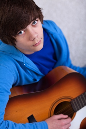 Portrait of teenager boy playing the guitar and dreaming away photo