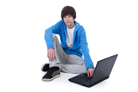 Casual teenager boy sitting on the floor with a laptop computer - isolated Stock Photo - 12074799