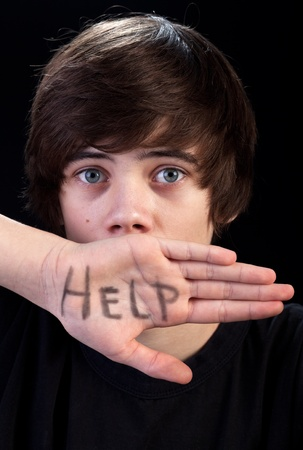 sad teen: Scared teenager boy needs help - body language and communication concept Stock Photo