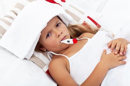 fieber: Krank kleines M�dchen mit einem Thermometer und einem K�hlakku im Bett Lizenzfreie Bilder