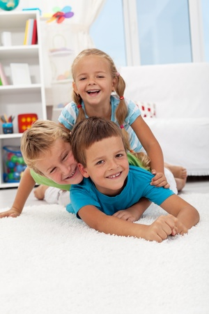 sibling: Playing happy children laying on the floor in a heap and laughing Stock Photo