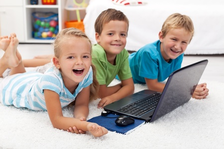 Happy kids with laptop computer laying on the floor photo