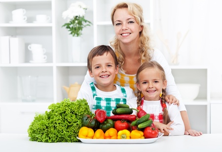 Woman and kids wearing aprons preparing vegetables in the kitchen photo
