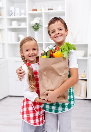 Happy healthy kids in the kitchen with the grocery bag full of vegetables photo