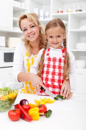 cutting vegetables: Chopping up vegetables with mom - little girl helping prepare a fresh meal