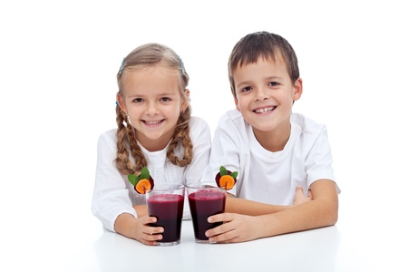 Happy smiling kids with fresh squeezed red vegetabless juice - isolated photo