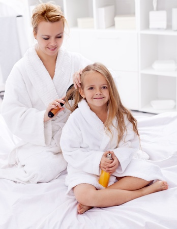 Drying and combing hair after bath - woman and little girl beauty ritual photo