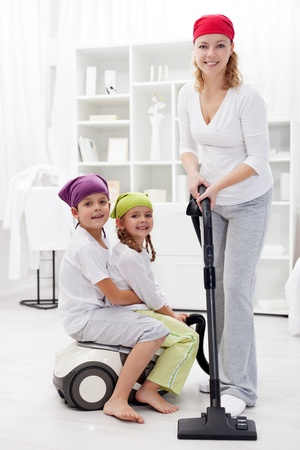 Happy family cleaning room with vacuum cleaner photo