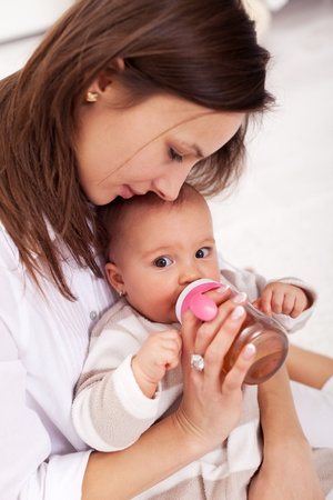 face of infant: Baby girl drinking from plastic bottle sitting in mother lap Stock Photo