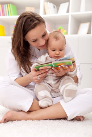 baby with mother: Look what a cute little ... woman and little girl watching a baby booklet