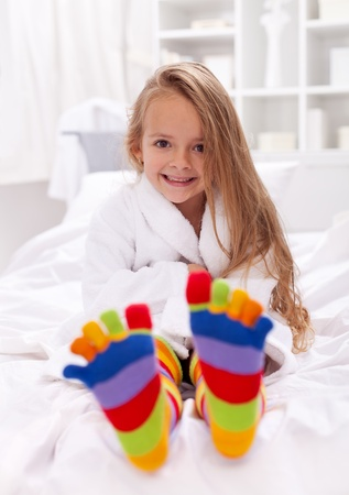 young girl feet: Happy little girl after bath wearing bathrobe and colorful sock