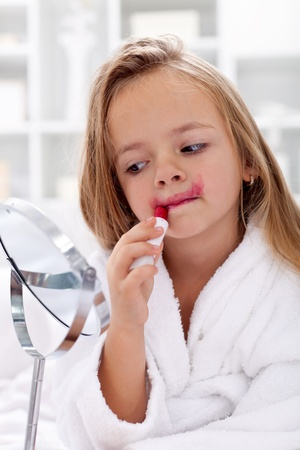 red bathrobe: Little girl trying moms lipstick - learning to be a modern woman