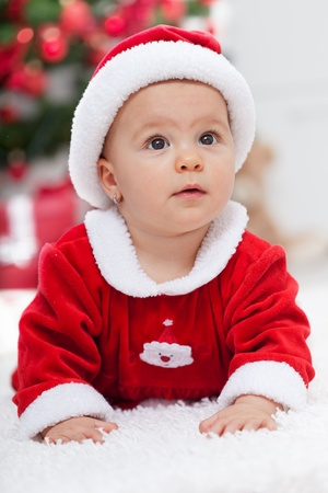 Christmas baby girl in front of the fir tree - closeup portrait photo