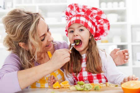 Eating fresh fruits is healthy - woman and little girl in the kitchen photo