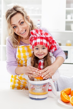 Healthy life - woman and little girl pressing fresh orange juice photo