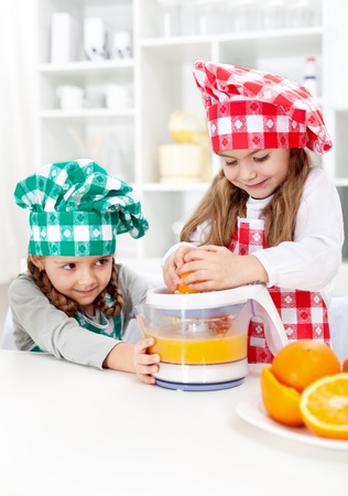 Little girls making fresh orange juice in the kitchen - healthy life education photo