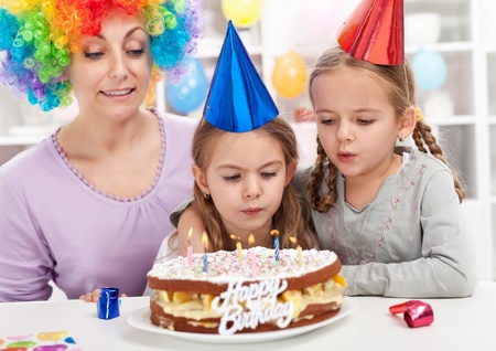 Birthday girl making a wish and blowing out candles on a cake Stock Photo - 12148623